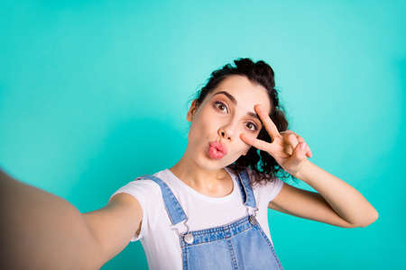 Self-portrait of her she nice attractive charming cute winsome wavy-haired girl showing v-sign near eye sending you kiss isolated on bright vivid shine green turquoise background