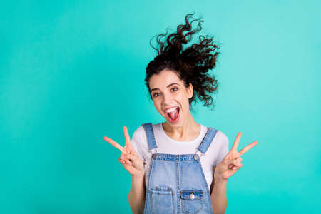 Close-up portrait of her she nice attractive charming cheerful cheery positive wavy-haired girl wearing blue overall showing v-sign isolated on bright vivid shine green turquoise background