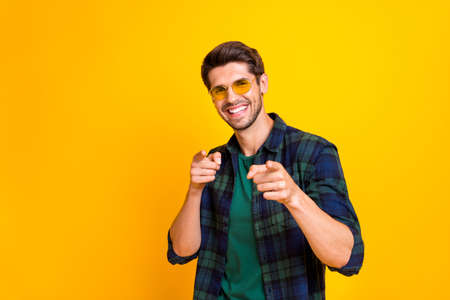 I pick you. Photo of funny guy indicating fingers on chosen candidate wear casual plaid shirt and sun specs isolated yellow color background 版權商用圖片