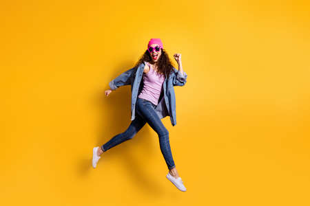 Full body photo of stylish wavy lady jumping high running quickly to shopping center wear casual trendy clothes isolated yellow color background