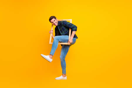 Full length photo of crazy guy holding wooden picture frame putting leg inside it wear casual checkered shirt and jeans isolated yellow color background Stock fotó