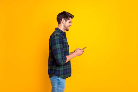 Profile photo of blogger guy holding telephone in hands checking instagram followers wear casual plaid shirt isolated yellow color background 写真素材