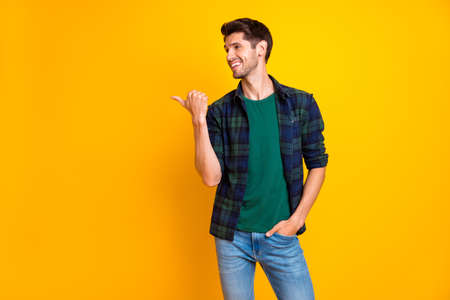 Photo of amazing guy indicating thumb finger to empty space wear casual plaid shirt and jeans isolated yellow color background