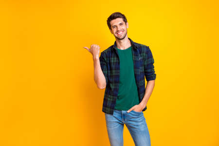 Foto di un ragazzo straordinario che indica il dito del pollice nello spazio vuoto indossa una camicia a quadri casual e jeans isolati con sfondo di colore giallo Archivio Fotografico