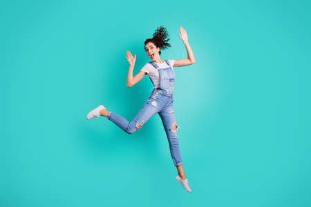 Full length body size view of her she nice attractive lovely cheerful cheery wavy-haired girl jumping celebrating having fun free time isolated on bright vivid shine vibrant green turquoise background