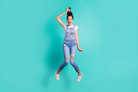 Full length body size view of her she nice attractive cheery crazy girl wearing blue overall jumping having fun making tail fooling isolated on bright vivid shine vibrant green turquoise background