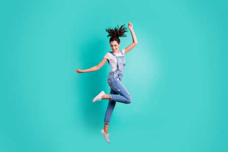 Full length body size view of her she nice-looking attractive charming cheerful careless girl wearing blue overall jumping having fun isolated on bright vivid shine vibrant green turquoise background
