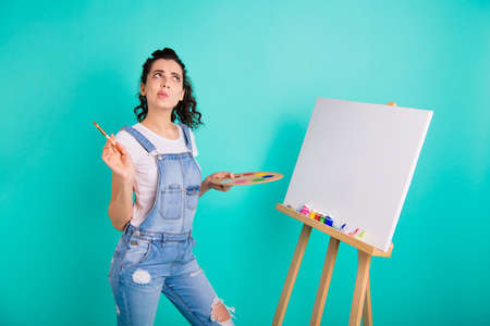 Portrait of nice attractive charming creative minded wavy-haired girl wearing casual holding in hands water color thinking creating new idea isolated on bright vivid shine green turquoise background