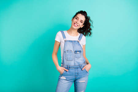 Portrait of her she nice attractive lovely charming cheerful content feminine wavy-haired girl wearing blue overall holding hands in pockets isolated on bright vivid shine green turquoise background
