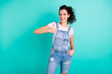 Portrait of her she nice-looking attractive lovely charming cute pretty cheerful cheery wavy-haired girl wearing blue overall showing thumbup isolated on bright vivid shine green turquoise background