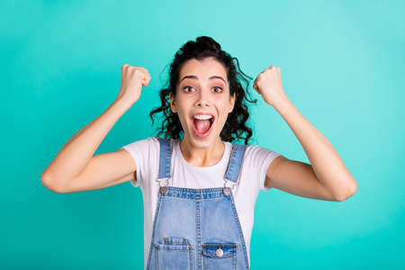 Close-up portrait of her she nice attractive lovely charming pretty cheerful cheery glad girl wearing blue overall celebrating good news isolated on bright vivid shine green turquoise background Archivio Fotografico