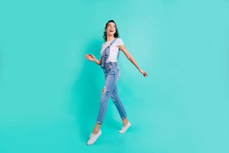 Full length body size view of her she nice attractive lovely cheerful cheery girl wearing blue overall strolling on tiptoe enjoying free time isolated on bright vivid shine green turquoise background
