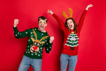 Portrait of crazy funny two lovers people wife husband brown hair celebrate victory raise fists scream yes wear christmas tree clothes eyeglasses jeans isolated over red color background Standard-Bild