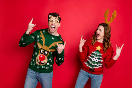 Portrait of foolish two family people wife husband brown hair scream have rock-and-roll show horned sign wear rudolf christmas tree design costume pullover sweater isolated over red color background Stock Photo