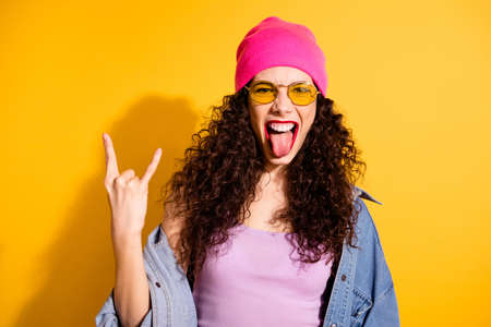Portrait of excited girl have free time weekends grimace true rocker wear modern pink cap tank-top isolated over yellow color background Stock Photo