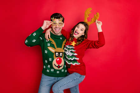 Portrait of crazy two people wife husband student hipster hug embrace wear brown comfort cozy pullover sweater with chritsmas tree design denim jeans eyewear isolated over red color background