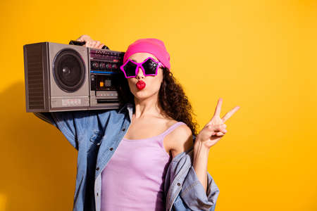 Photo of flirty lady with tape recorder on shoulder showing v-sign sending air kiss wear casual trendy clothes isolated yellow color background