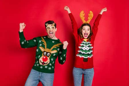 Porträt von verrückten lustigen Zweifamilienfrauen, braunen Haaren, die den Sieg feiern, die Fäuste schreien, ja, tragen Sie Weihnachtsbaum-Design-Pullover-Jeans-Kostümbrille einzeln auf rotem Farbhintergrund Standard-Bild