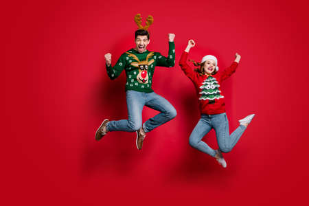 Full size photo of funky lady and guy jumping excited by x-mas prices wear ugly ornament jumpers and headwear isolated red color background
