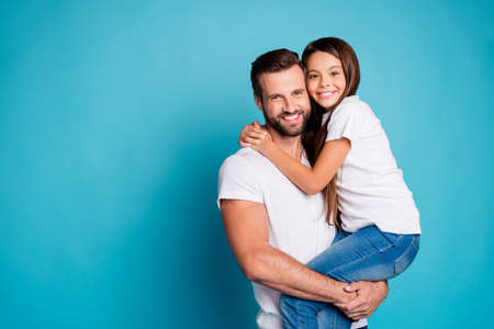 Portrait of lovely man with brunet hair cut holding his daughter having long hair wearing white casual t-shirt denim jeans isolated over blue background