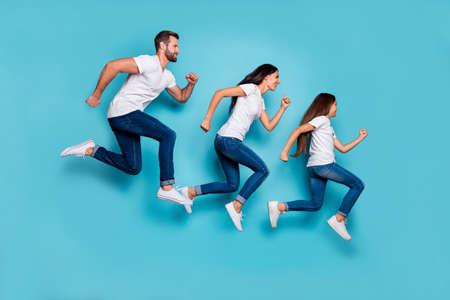 Foto del tamaño del cuerpo de cuerpo entero de la familia deportiva corriendo siendo saludable y hermoso mientras está aislado con fondo azul Foto de archivo