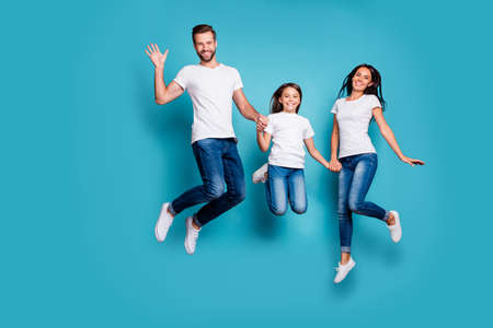 Full length body size photo of funny funky cheerful glad family jumping in front of camera while isolated with blue background