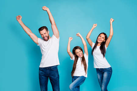 Photo of daddy mommy and small lady raising fists air rejoicing wear casual, outfit isolated blue background