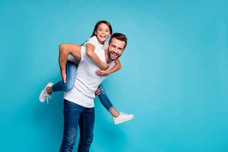 Portrait of cheerful people laughing piggyback wearing white t-shirt denim jeans isolated over blue background 版權商用圖片