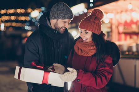 Photo of guy giving pretty lady his x-mas giftbox with red bow newyear, tradition wearing warm coats knitted caps and scarfs outdoors