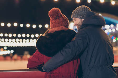 Rear back behind view portrait of his he her she nice attractive charming friendly cheerful cheery engaged couple wearing warm outfit, coat hat cap headwear spending December outdoor