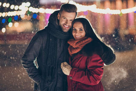 Photo of two people in love visiting central city park at x-mas eve standing close making wishes wearing warm winter jackets and scarfs outside