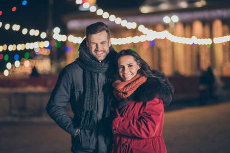 Photo of two sweethearts pair in love attending city park at newyear, midnight frosty weather standing close wearing warm winter jackets outdoors