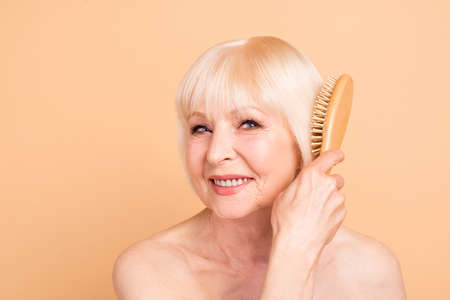 Close-up portrait of her she nice attractive lovely well-groomed cheerful cheery gray-haired lady combing time for yourself isolated over beige background