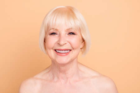 Close-up portrait of her she nice-looking attractive well-groomed shine cheerful cheery gray-haired lady isolated over beige pastel background