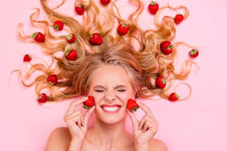 Cerrar la parte superior por encima de la foto de vista de ángulo alto hermosa ella su dama acostada entre frutas fresas cabello largo acción fuerte de la mascarilla facial exfoliante de frutas crema humectante loción aislado fondo rosa