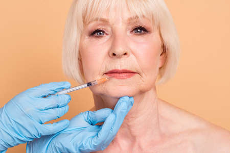 Close up photo attractive beautiful mature she her aged lady surgeon medic nurse hold hands arms getting hyaluronic cosmetology injecting make lips bigger isolated pastel beige background