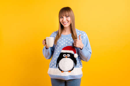 Best choice for drinking on Christmas Eve concept. Photo of pretty dreamy cheerful hipster in knitted retro jumper holding cup of tasty eggnog in hand make finger up isolated vivid color background Stock Photo