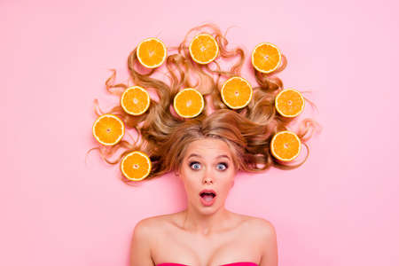 Close up top above high angle view photo beautiful funny funky she her lady, lying down oranges long curly wavy hair wondered interested asking isolated pink background Фото со стока