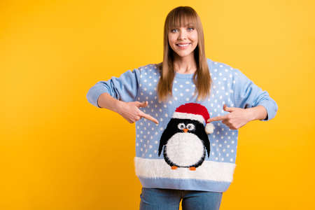 Ill take part in ugly sweater party event concept. Photo of cheerful teen lady demonstrating pattern with comic cute sweet lovely animal in santa claus cap on outfit isolated bright color background Stock Photo