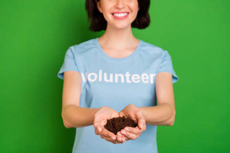 Close-up cropped view portrait of nice attractive cheerful kind girl wearing, blue t-shirt holding in hands natural soil rescue save forest isolated over bright vivid shine vibrant green background