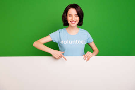 Portrait of her she nice attractive cheerful cheery confident girl wearing blue t-shirt pointing at copy empty blank place space isolated, over bright vivid shine vibrant green background