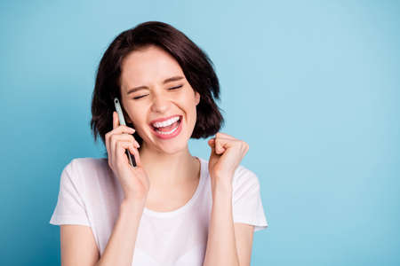 Close-up portrait of nice attractive lovely glad excited cheerful cheery satisfied girl talking on phone good news isolated on bright vivid shine vibrant blue turquoise color background Stockfoto - 130353834