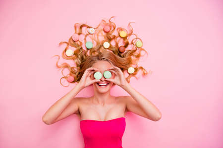 Vertical side profile top above high angle view photo beautiful she her lady lying down sweets ideal hair hands arms hide eyes spectacles specs wear formalwear dress isolated rose pink background Фото со стока