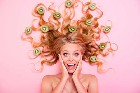 Close up top above high angle view photo beautiful she her lady lying down full kiwi fruits pretty long curls healthy vitamin product complex hairdo novelty want try buy buyer isolated pink background