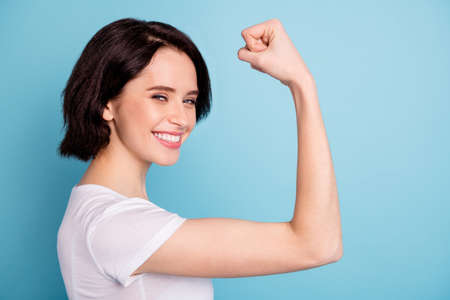 Close-up profile side view portrait of her she nice attractive lovely winsome, cheerful cheery glad girl showing arm muscles isolated on bright vivid shine vibrant blue turquoise color background