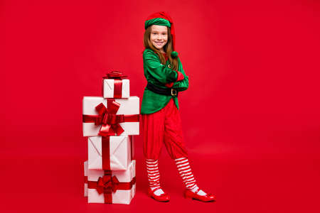 Full length body size view of her she nice attractive content cheerful cheery funny pre-teen elf folded arms winter holly jolly tradition sale discount isolated over bright vivid shine red background