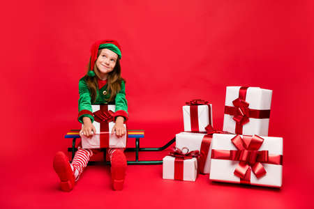 Cheerful pre-teen elf holding christmas gift isolated over red background Stock Photo