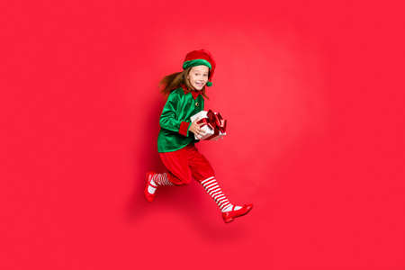 Full length body size view of nice attractive cheerful cheery glad funny funky positive small little pre-teen elf carrying holding in hands purchase isolated over bright vivid shine red background Stock Photo