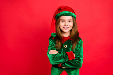 Portrait of cheerful elf girl in hat with her hands crossed smiling ready to help in christmas night wearing cap costume isolated over red background
