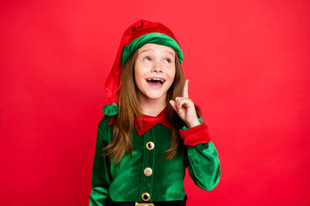 Portrait of surprised liitle kid elf raising her index finger having solution screaming wow omg wearing greem elf costume hat cap isolated over red background